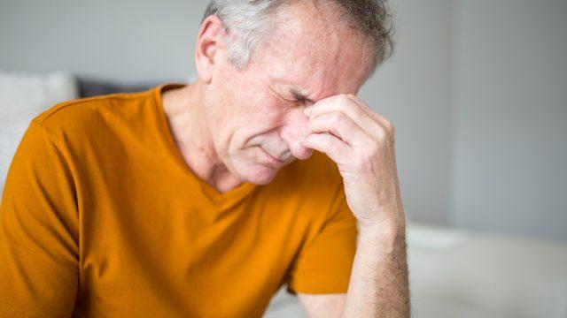 Portrait of senior man suffering from migraine or stroke