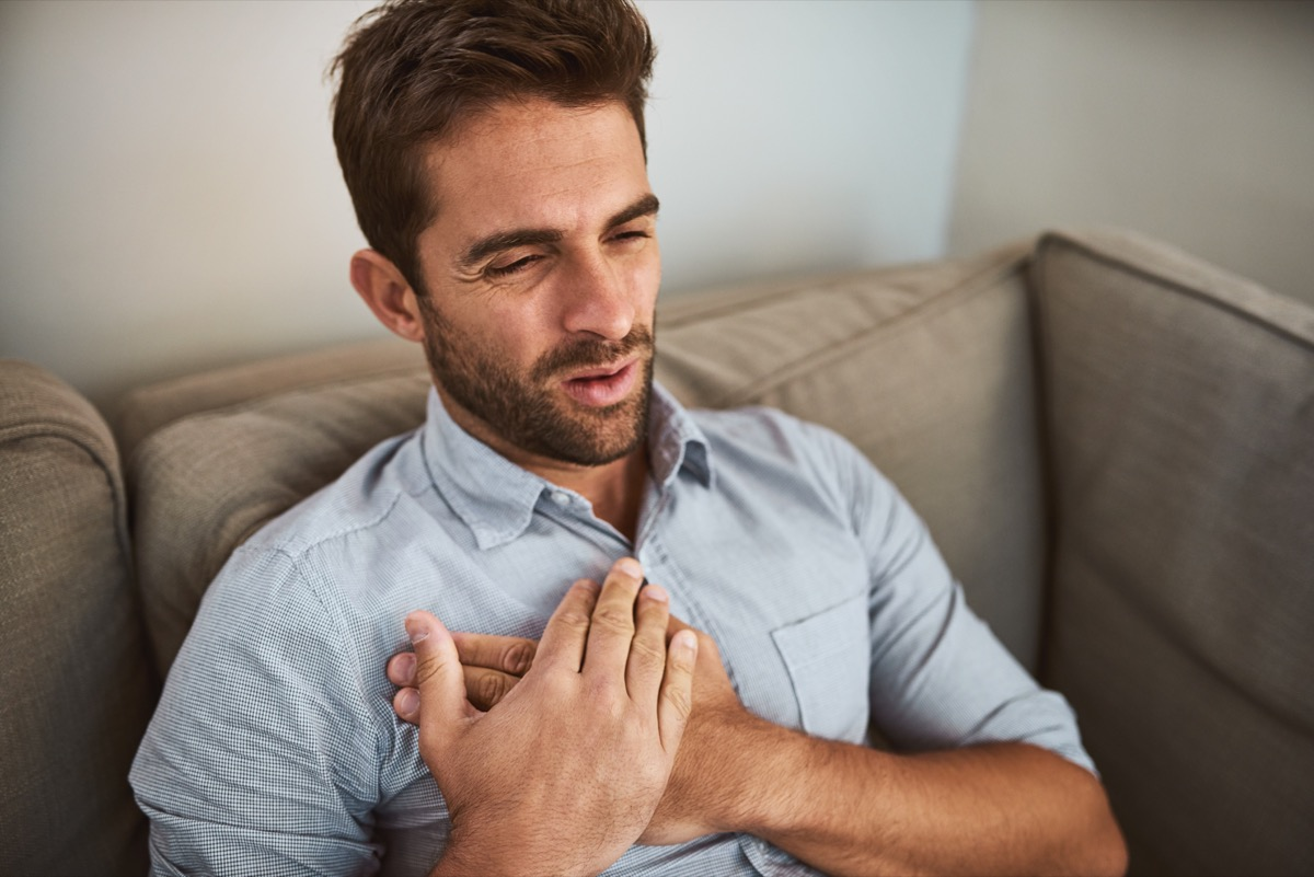 Shot of an uncomfortable looking young man holding his chest in discomfort while being seated on a couch at home
