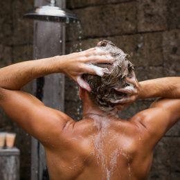 A man washing his hair while showering.
