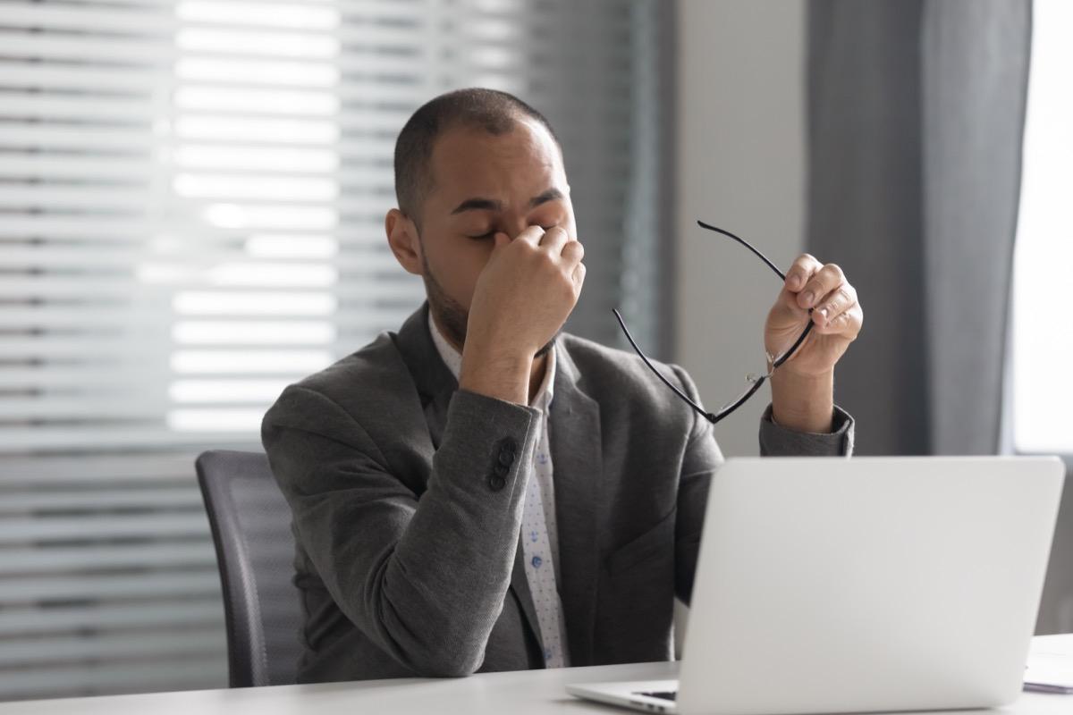 man sitting at laptop rubbing eyes