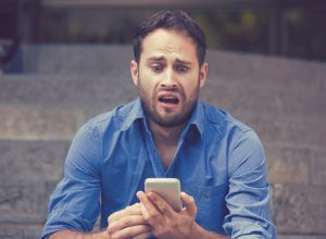 A young man looking at his smartphone with a horrified look on his face.