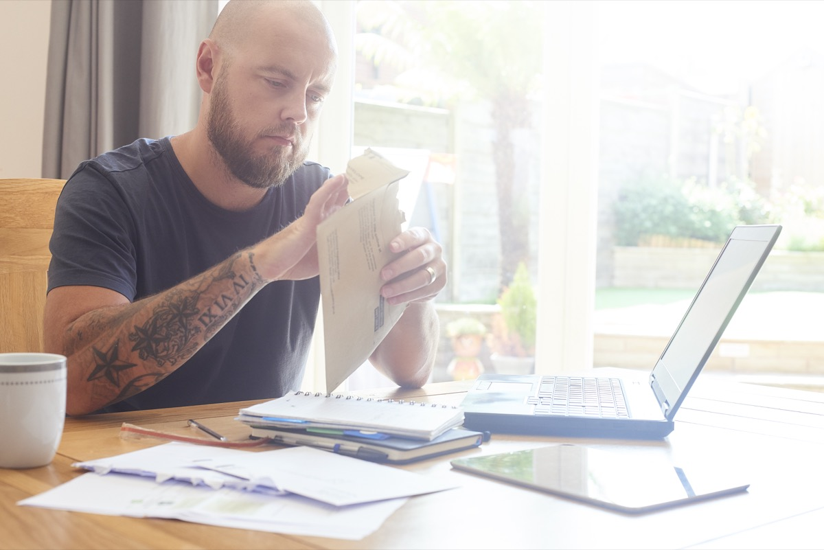Man sat at dining room table working from home or sorting out home finances