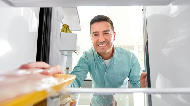 middle-aged man taking meat out of the fridge