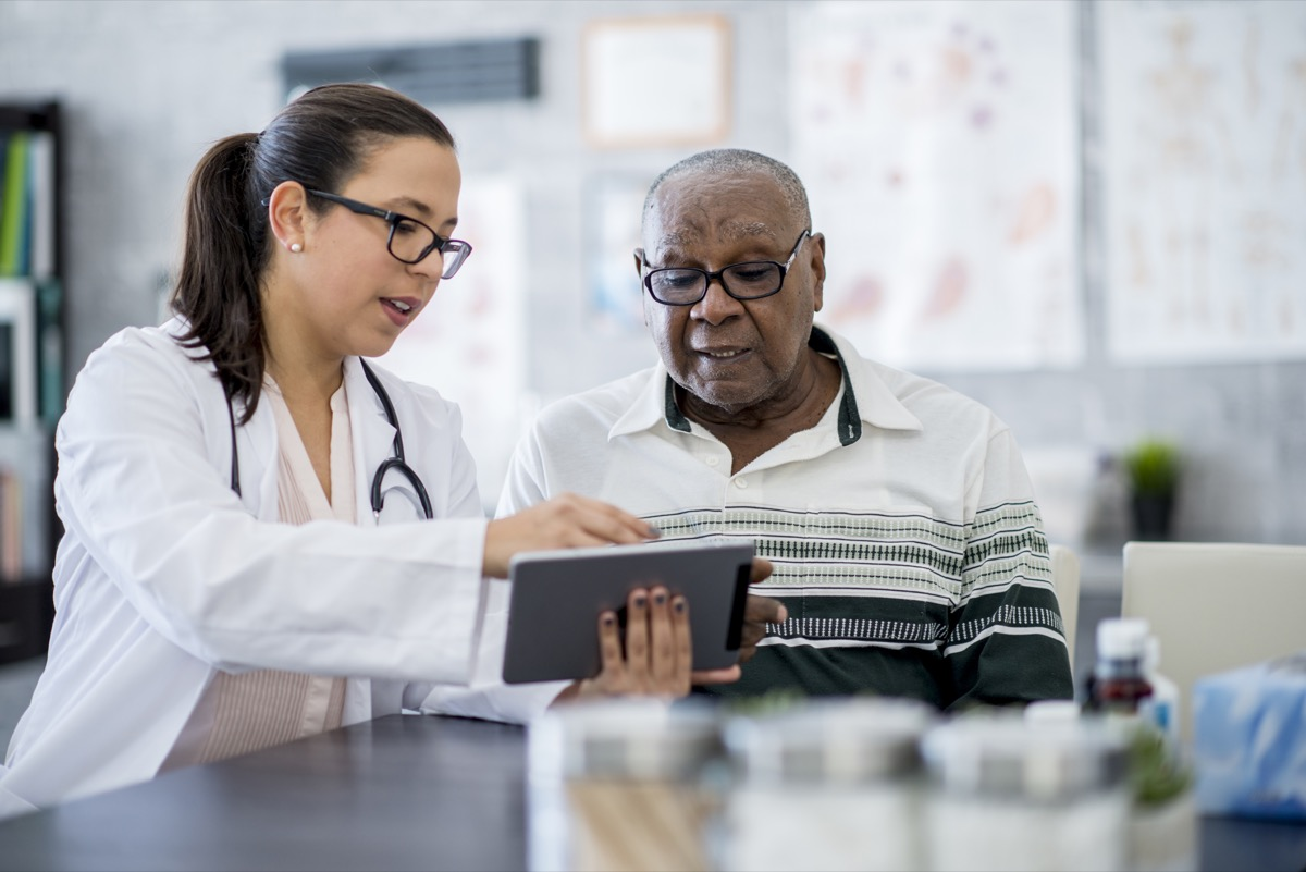 A senior man is indoors in a hospital room. He is watching his female doctor using a tablet computer. She is explaining a medication schedule to him.