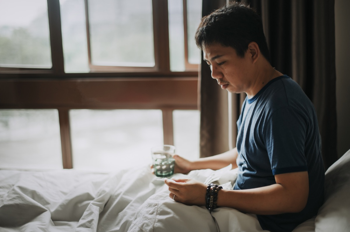 male sick illness at home and checking his body temperature using a thermometer and taking medicine with water on a bed