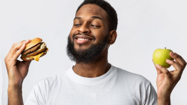 man holding a burger and an apple