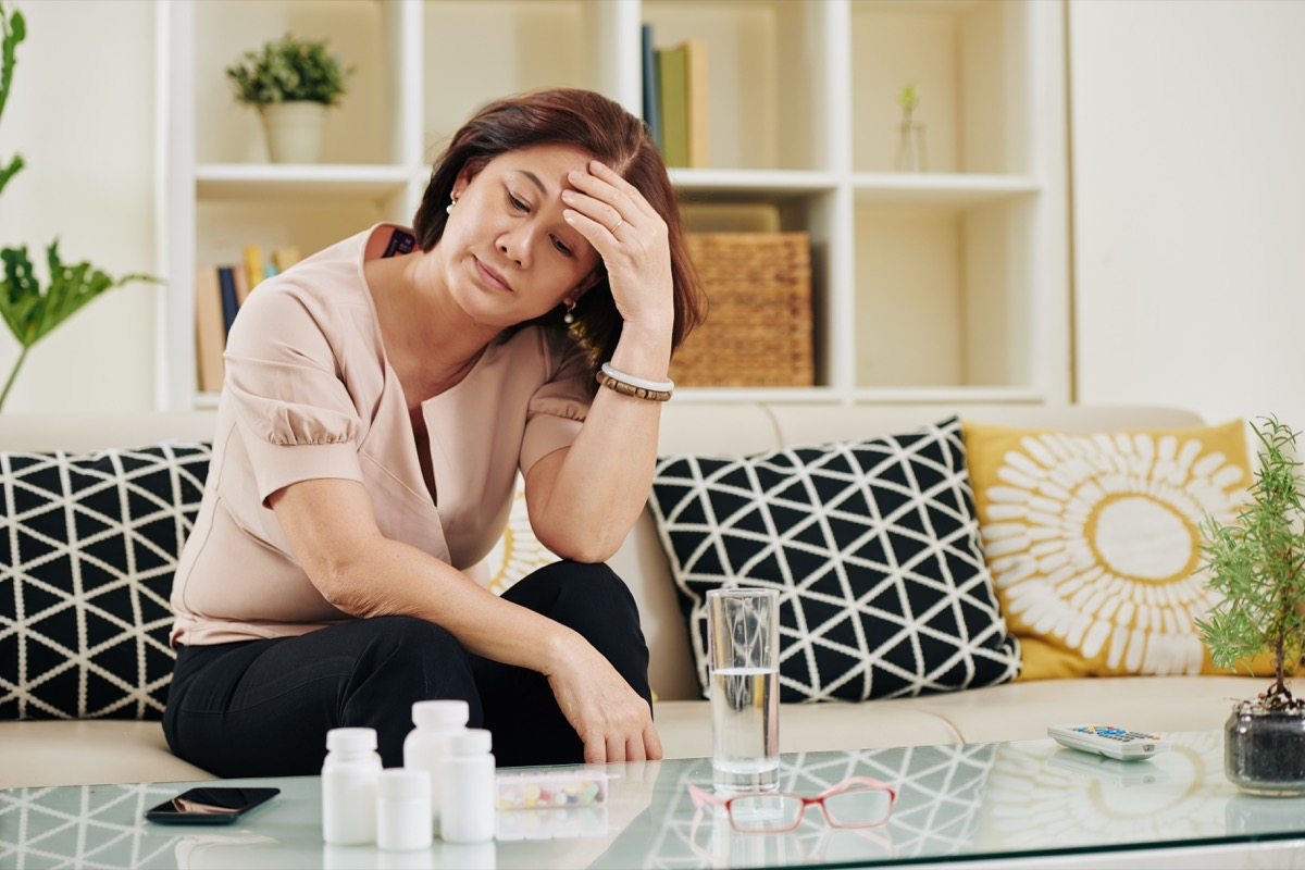 Stressed sad mature woman looking at pile of medicine in table in front of her