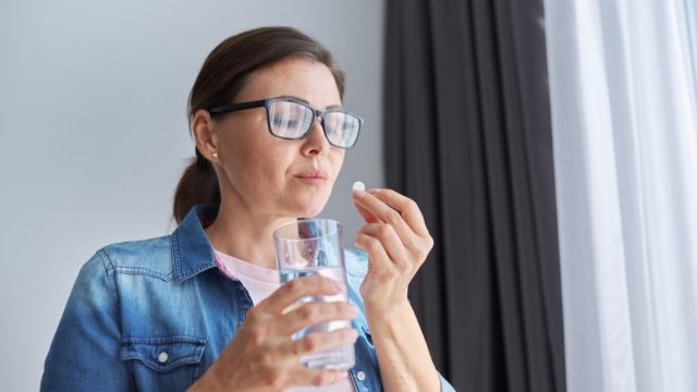 middle aged brunette woman taking a pill