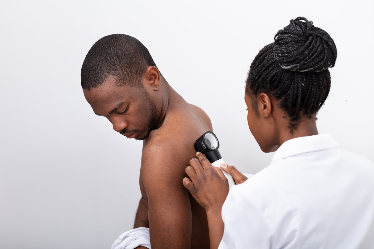 Young Doctor Examining Mole On Man's Back With Dermatoscope
