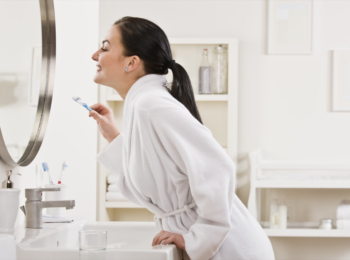 A young woman is standing in front of the bathroom mirror and brushing her teeth. Horizontally framed shot.