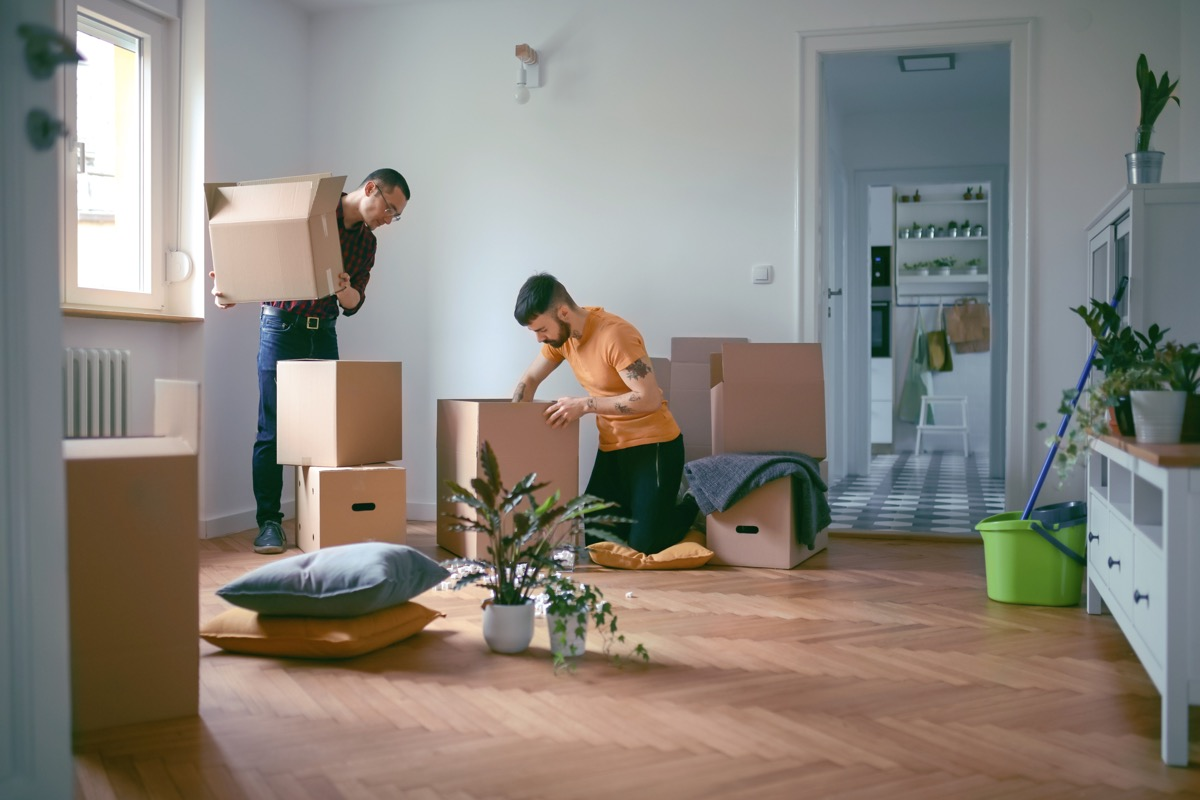 couple unpacking cardboard boxes and moving in a new home