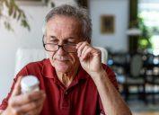 Senior man taking prescription medicine at home