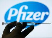Syringe in shadow over Pfizer logo
