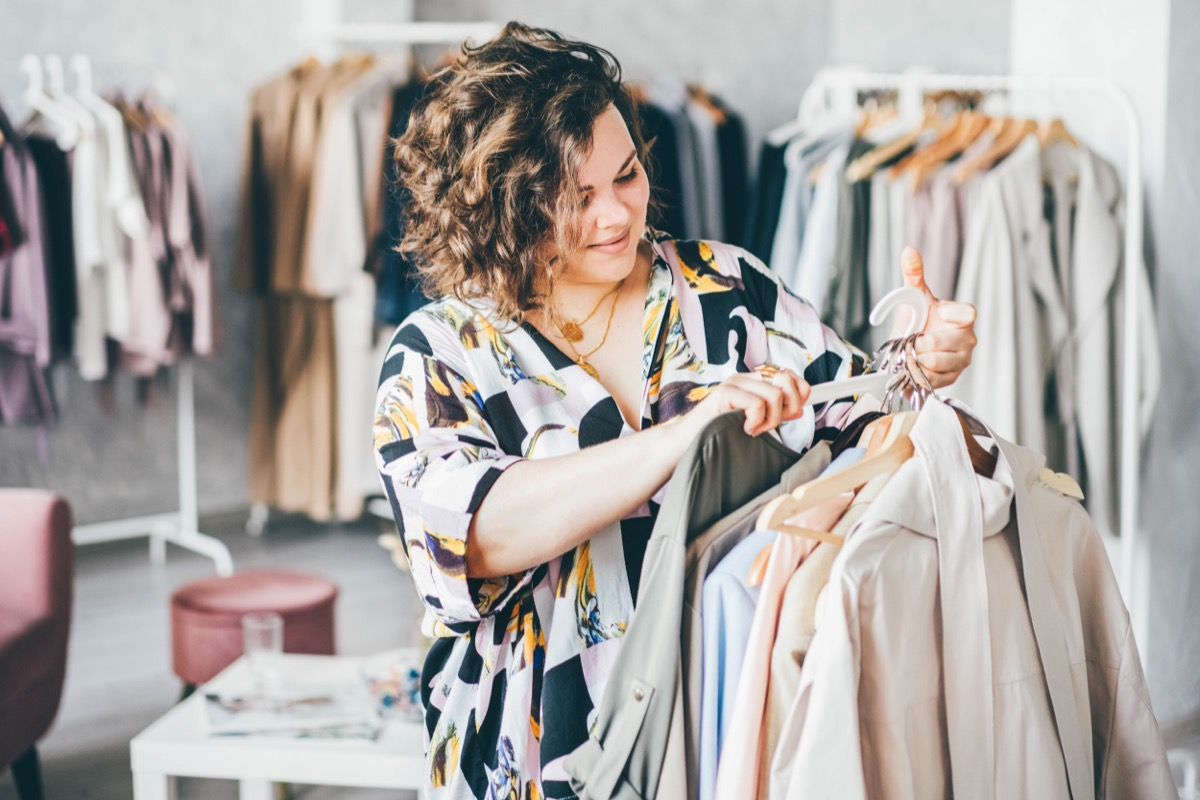 plus size woman with curly hair shopping for clothing