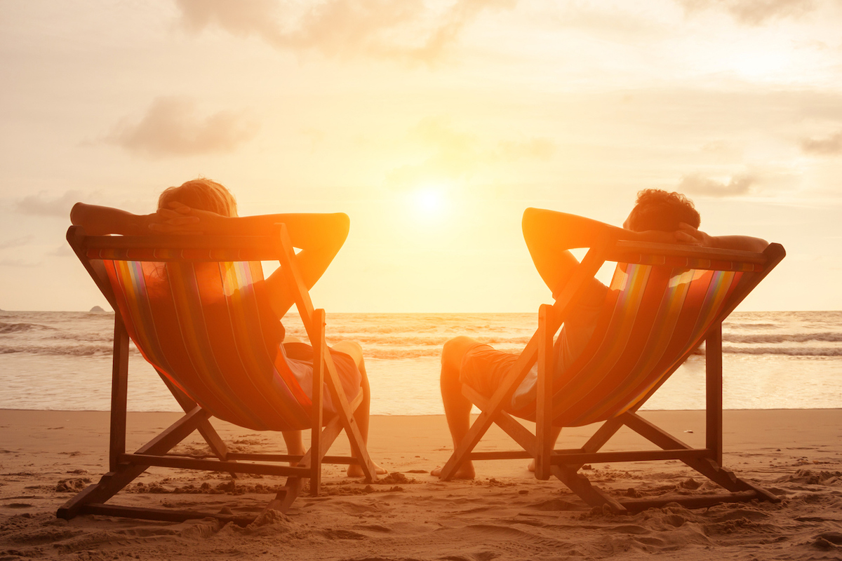 Silhouette of happy young retired couple sitting in deck chairs on the beach at sunset