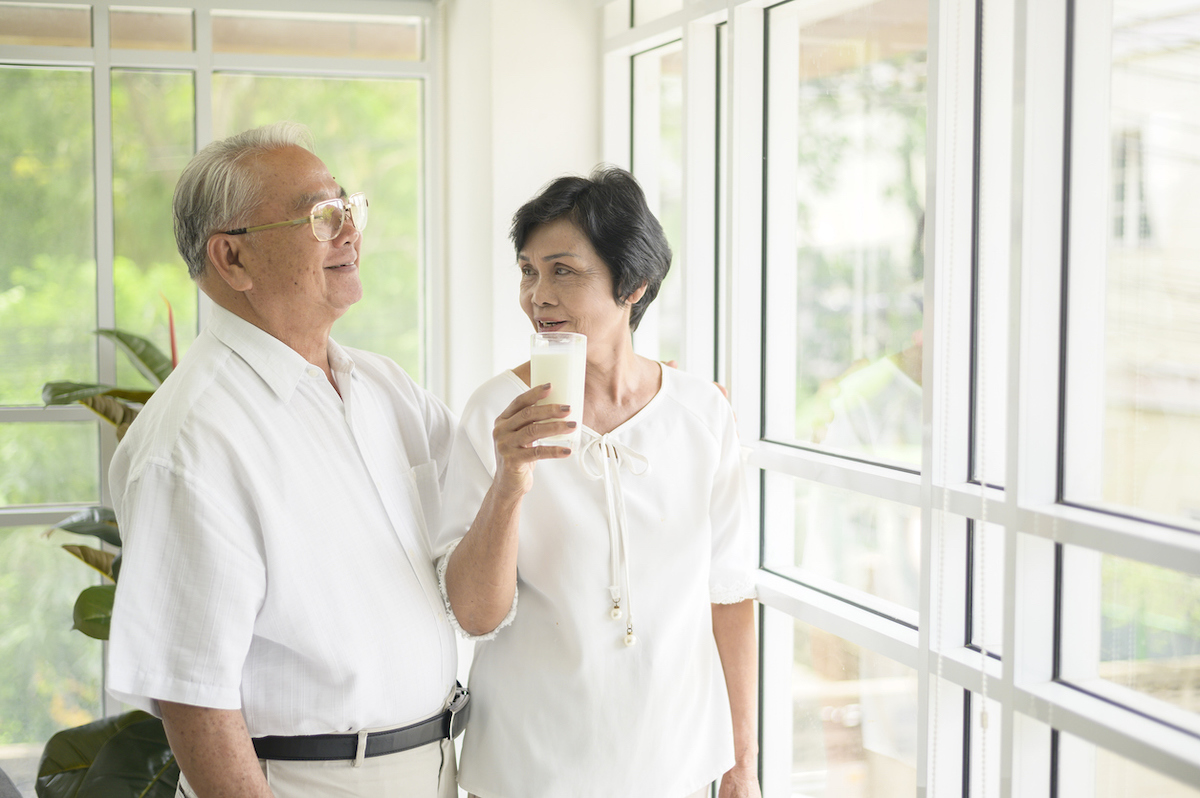 Happy elderly couple drinking milk and spending time together at home