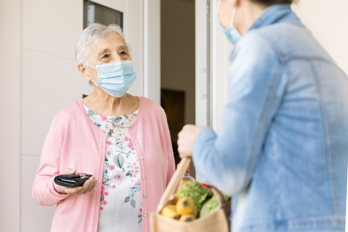 Woman delivering groceries to senior woman during quarantine