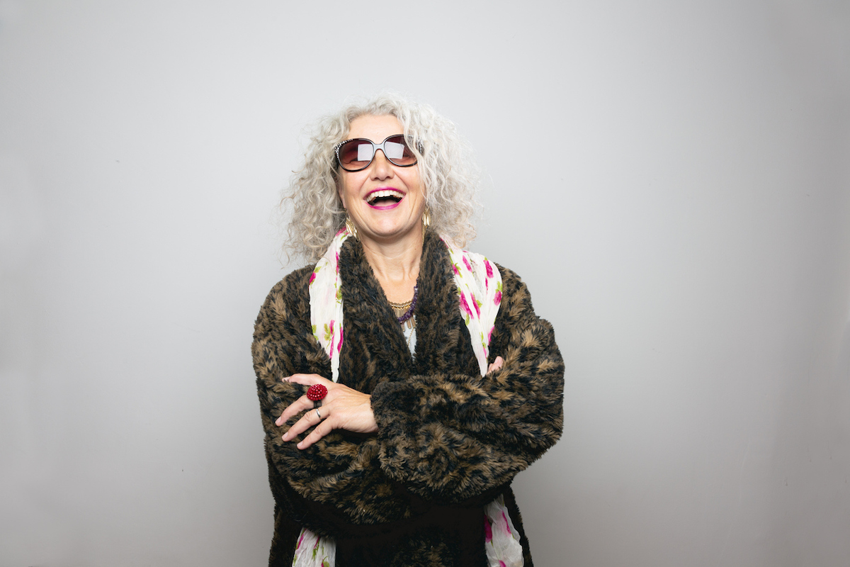 Cool mature woman, wearing sunglasses and a coat made from artificial fur, wearing scarf with floral pattern and a lot of jewelry, standing in front of grey background