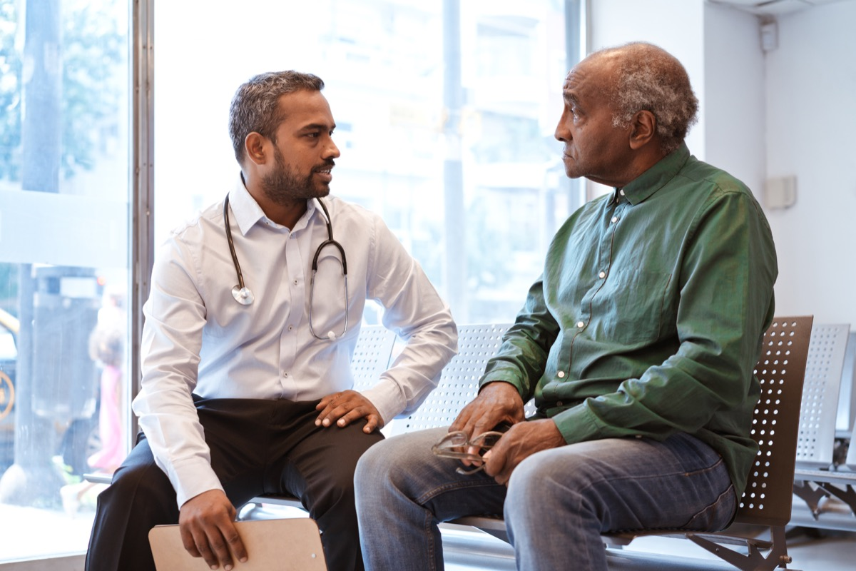 Doctor talking to senior patient sitting in waiting room. Serious man is staring at healthcare worker at hospital. They are against window.