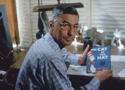 American author and illustrator Dr Seuss (Theodor Seuss Geisel, 1904 - 1991) sits at his drafting table in his home office with a copy of his book, 'The Cat in the Hat', La Jolla, California, April 25, 1957. (Photo by Gene Lester/Getty Images)