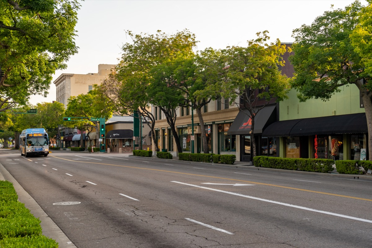 bus driving down street, fullerton, california, street lined with trees