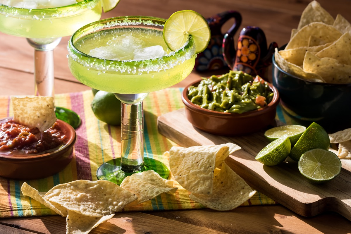 margarita in glass, salt on rim, guacamole and chips on table
