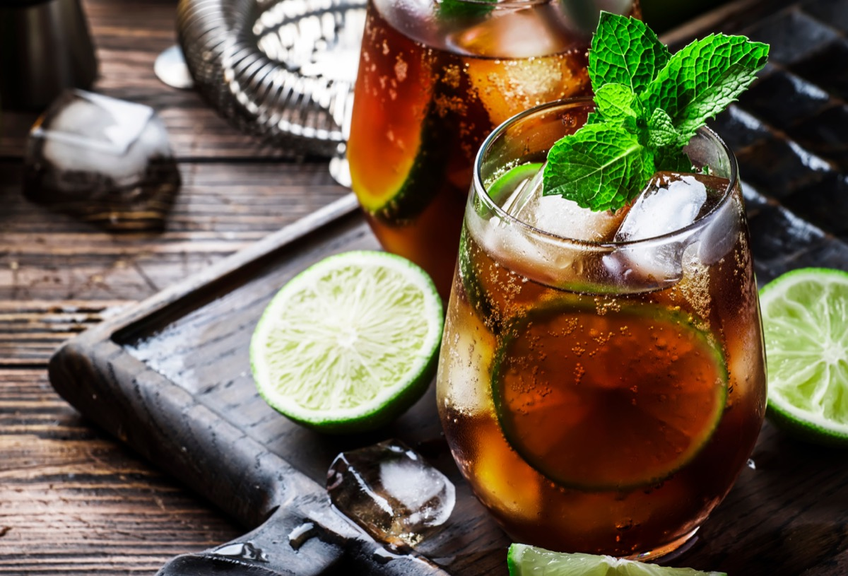 rum and cola, alcoholic beverage with lime, glass on a table