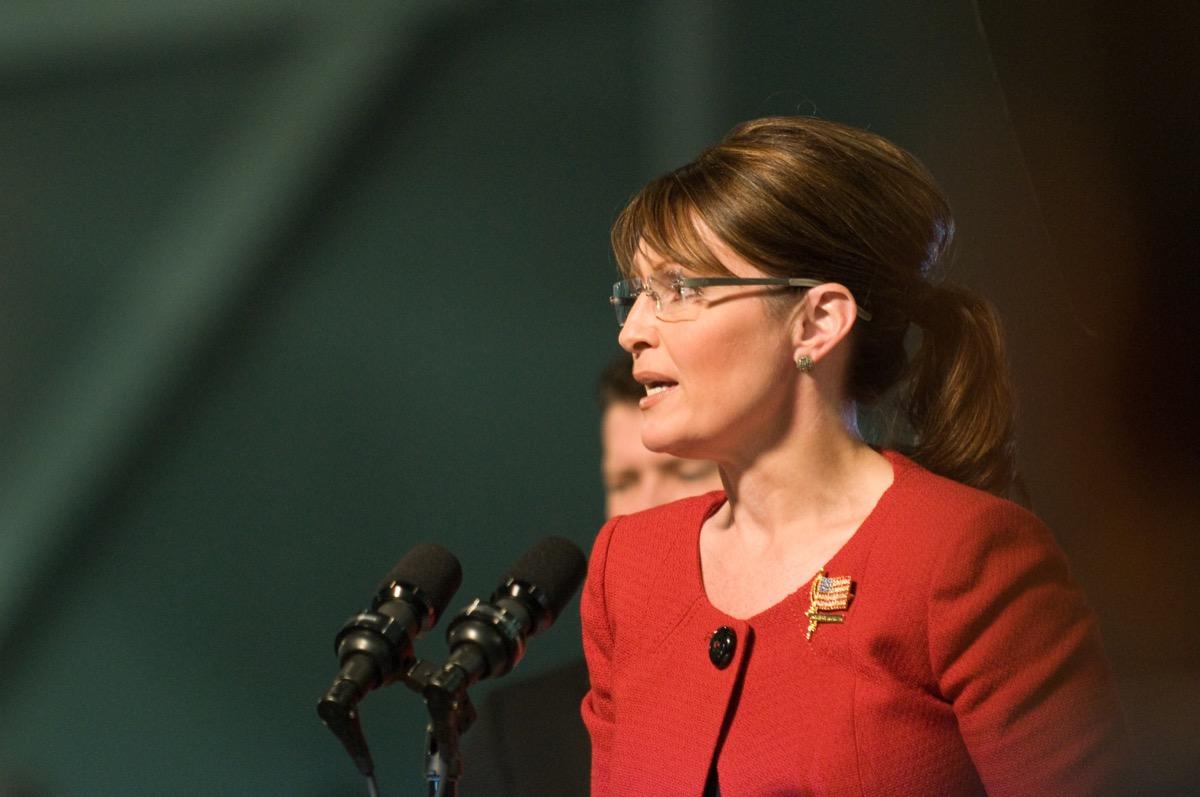 sarah plain speaking at a podium, palin wearing red