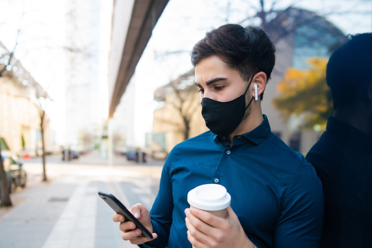man with face mask and coffee looking at his phone outside