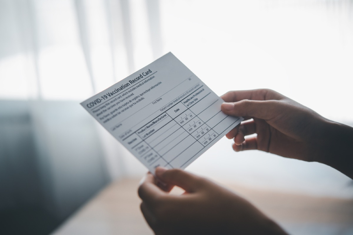 close up of person holding covid vaccination card