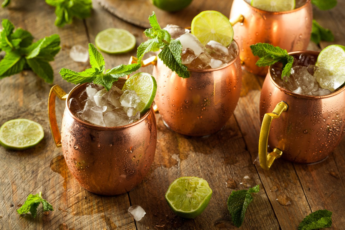 whiskey ginger, ginger beer, clear glass on wooden table, lime
