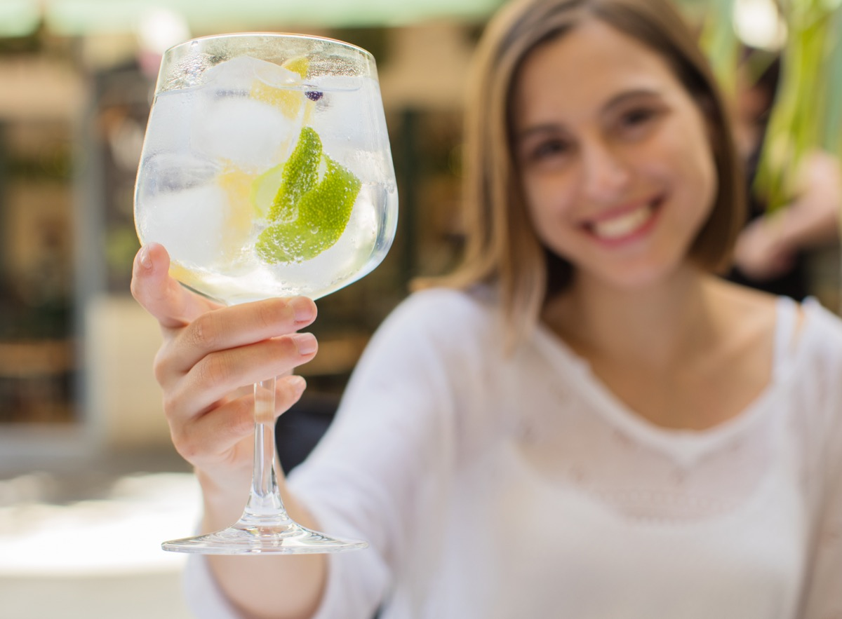 young woman holding drink, gin and tonic, in glass