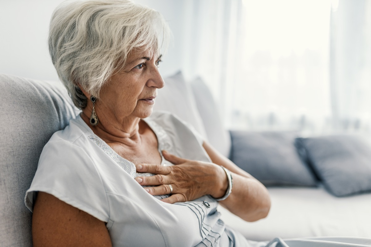 aged woman having heart attack. Woman is clutching her chest, acute pain possible heart attack. Heart disease. People with heart problem concept