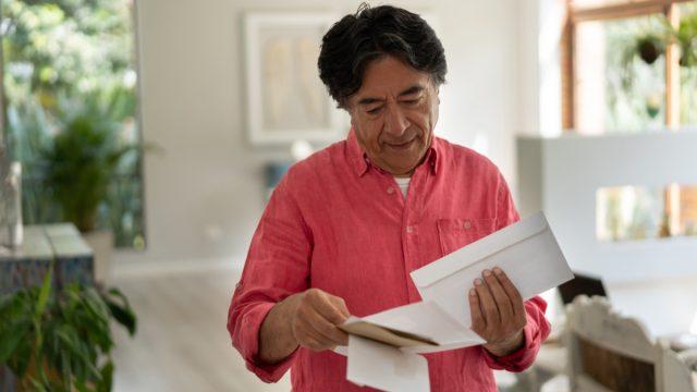 Cheerful senior man at home looking at his mail