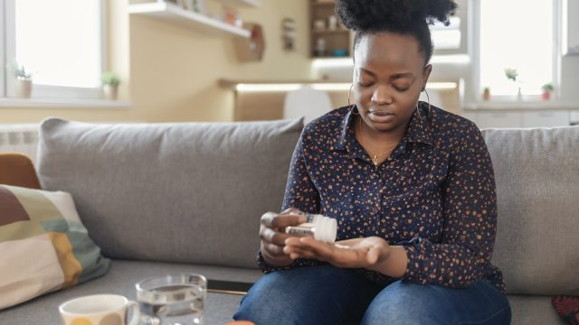 Woman Taking Medication for Her Illness