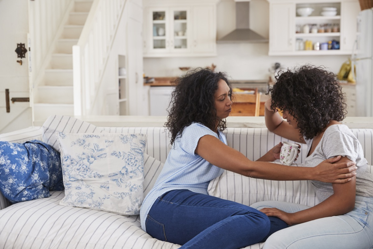 Mother Talking With Unhappy Teenage Daughter On Sofa