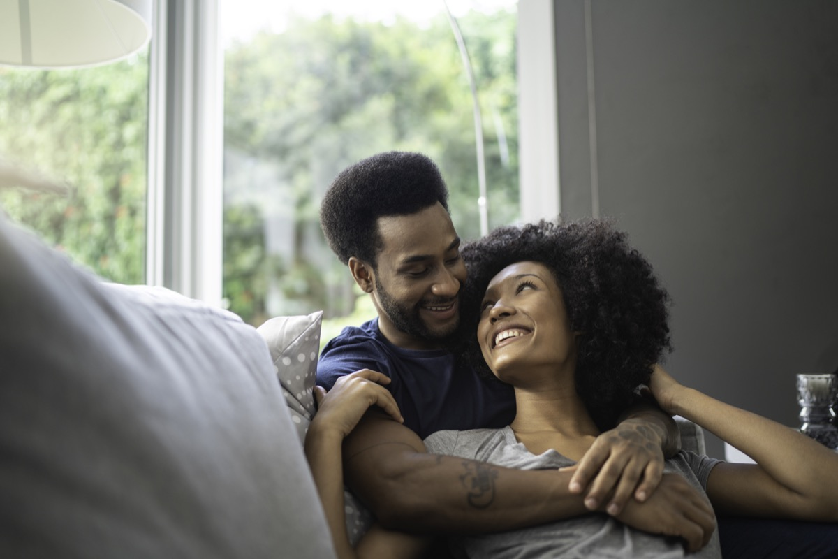 couple lying down and having romantic moment on couch