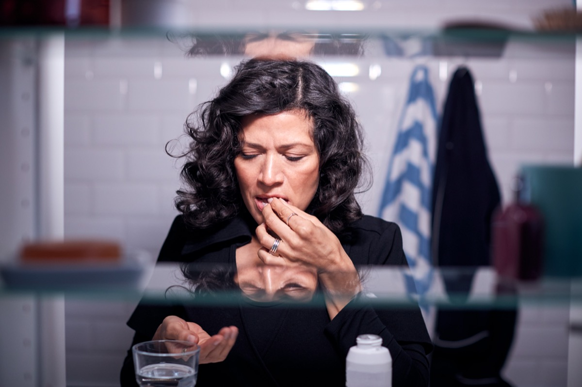 View Through Bathroom Cabinet Of Mature Woman Taking Medication With Glass Of Water
