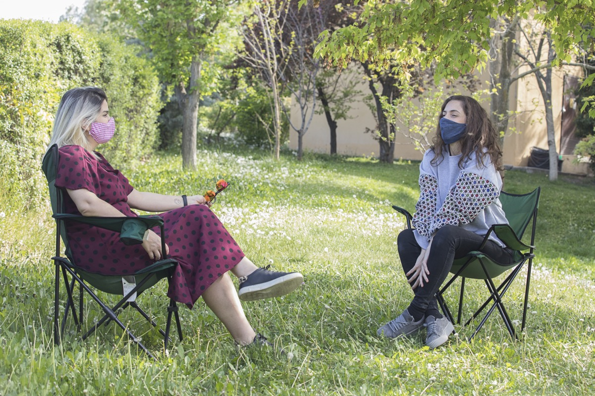 two women sitting outdoors with home made face masks.