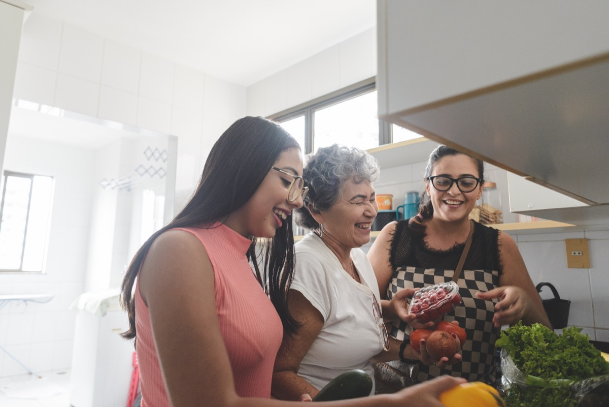 Grandmother, mother and daughter unpacking groceries in the kitchen