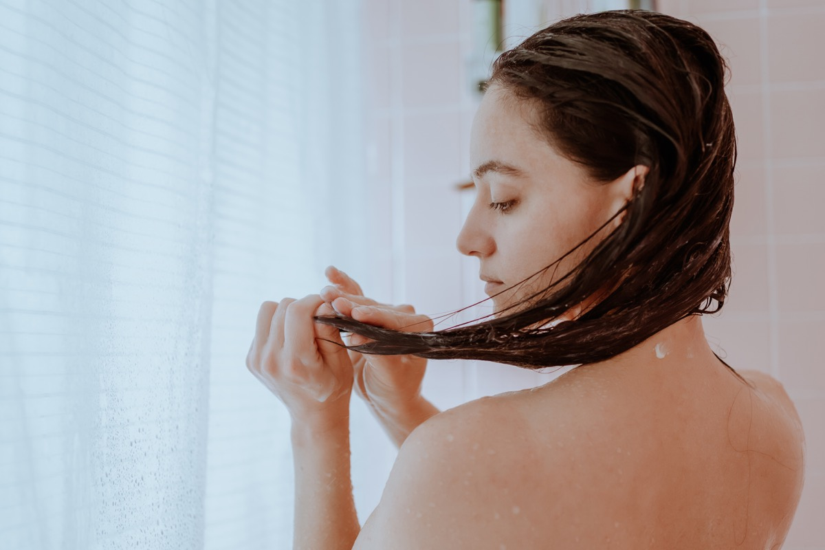 Woman taking a shower and washing her hair at home