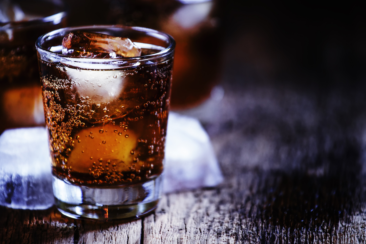 bourbon cola with whiskey and ice cubes on vintage wooden background