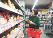 young woman buying snacks at supermarket
