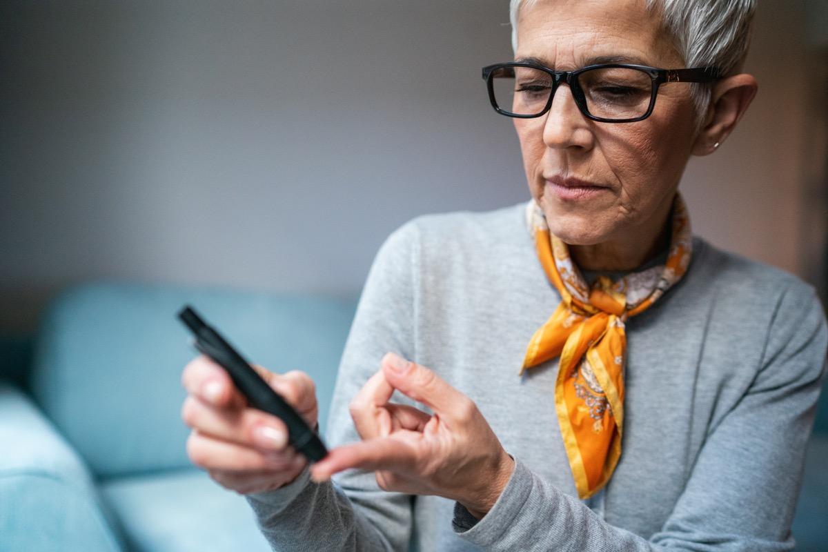 Modern Senior woman doing Diabetes blood test at home