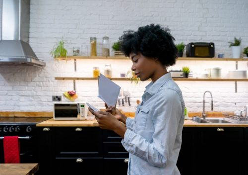 woman at home reading the mail - lifestyle concepts