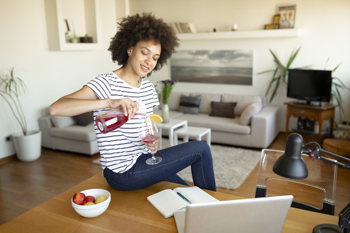 woman is relaxing, enjoying and having fun at home with some alcoholic beverage