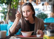 brunette woman eating soup in restaurant