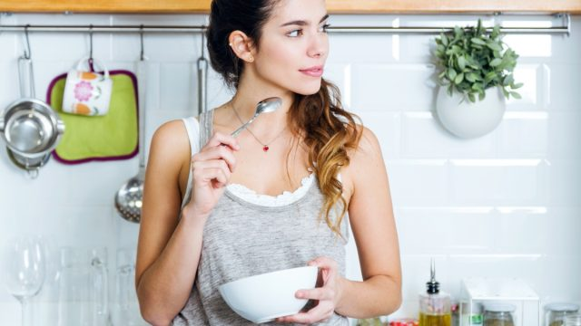 young woman in gray tank top eating from white bowl in modern kitchen