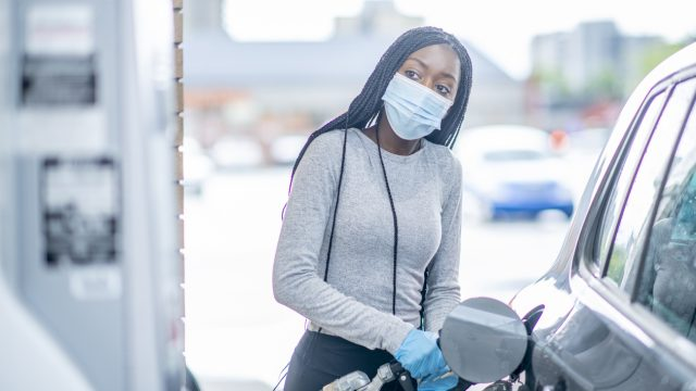 A young woman wearing a face mask and gloves fills her car's gas tank.