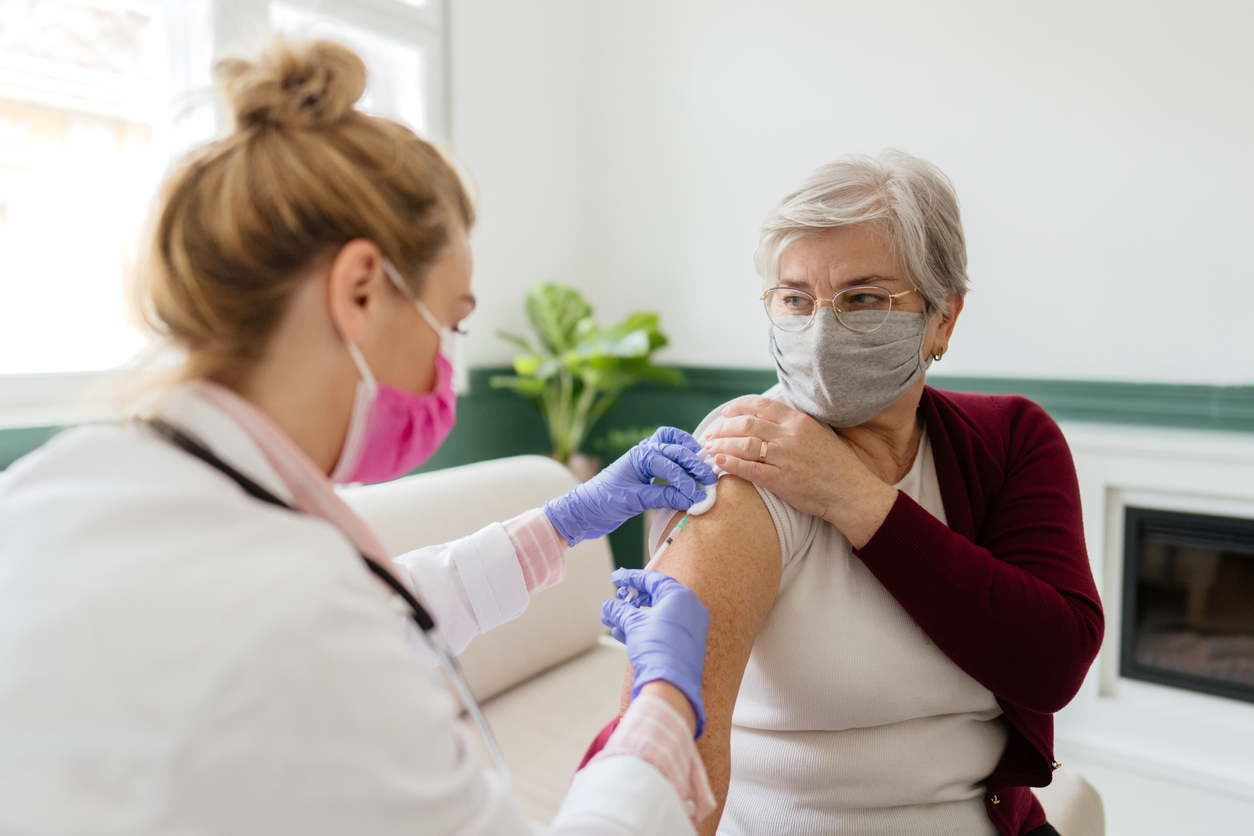 A senior woman receiving a COVID-19 vaccination from a female healthcare worker